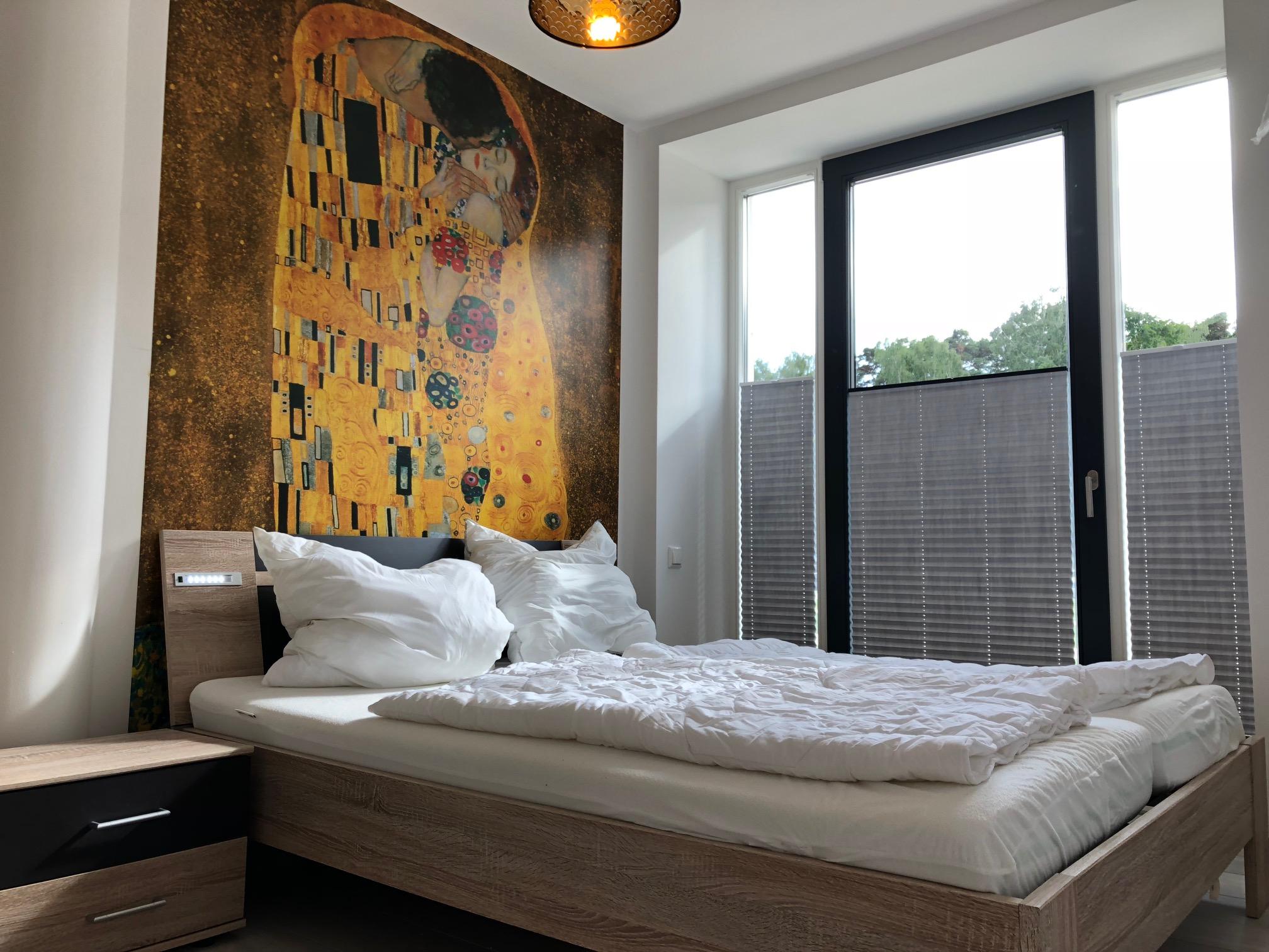 landseitiges Schlafzimmer mit Doppelbett, Verdunklungsplissees, großem Kleiderschrank mit Spiegeltüren