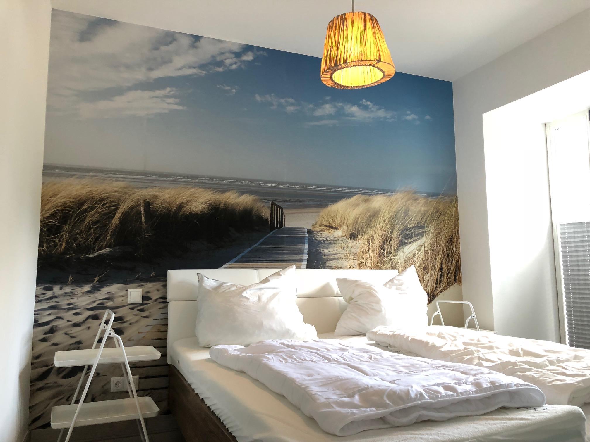 seeseitiges Schlafzimmer mit Doppelbett, Verdunklungsplissees, eigener Terrasse und direktem Strandzugang